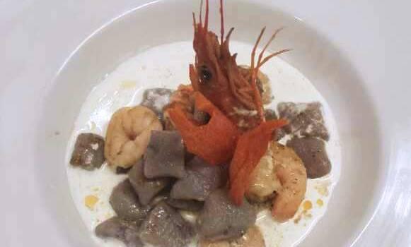 Gnocchi di patate viola con demi glȃce e gamberi su crema di bufala campana